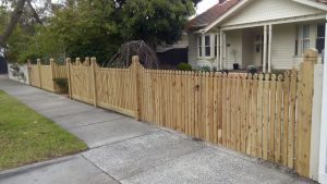 """Exposed cypress post picket fence with 3 """"Tulip"""" pickets rising to each post.  Recessed single gate and flush double gate."""